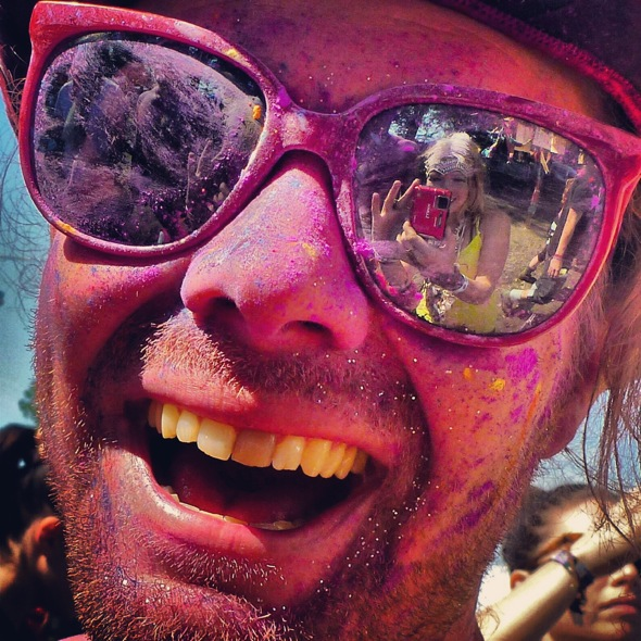 A close up of the paint splattered festival goer Ross Day at The Secret Garden Party 2012 with Lucie Galt reflected in his sunglasses