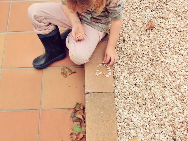 Girl making heart witth stones