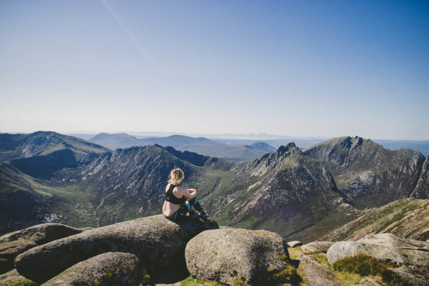 Travel blogger Kathi Kamleitner sitting at the top of Goatfell, the highest mountain on the Isle of Arran in Scotland.