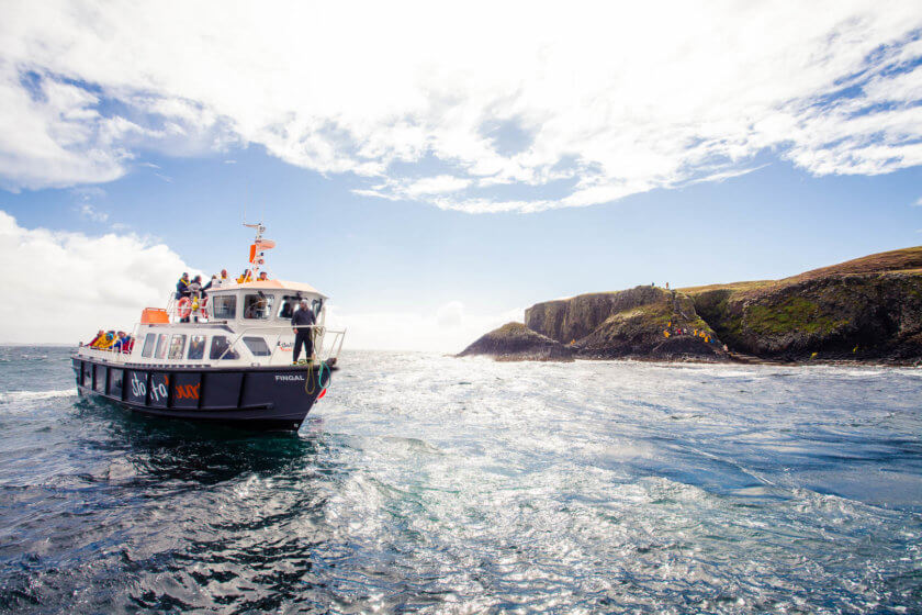 A boat from Staffa Tours off the shore of the Isle of Staffa near Fingal's Cave in Scotland.