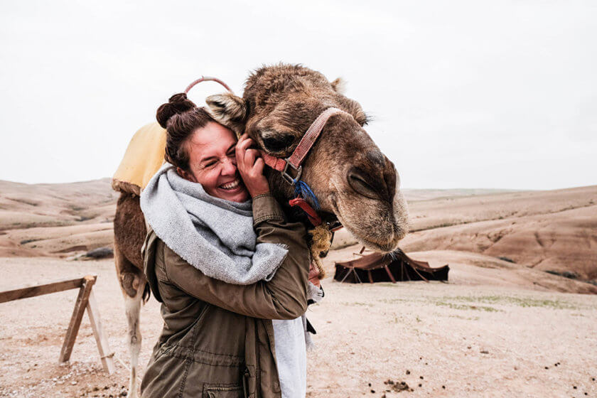 Woman hugging a camel in Morocco