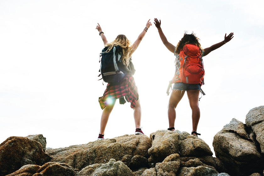 Two women with backpacks standing on a rock.