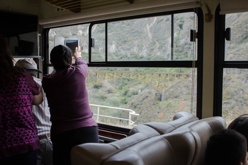 A woman taking photos of the view from aboard the Tren de la Libertad in Ecuador.