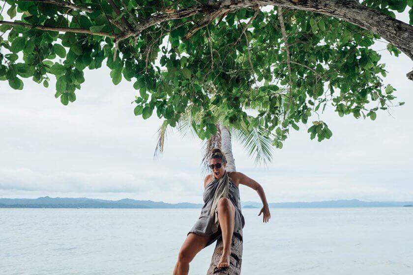 Woman trying to climb a palm tree